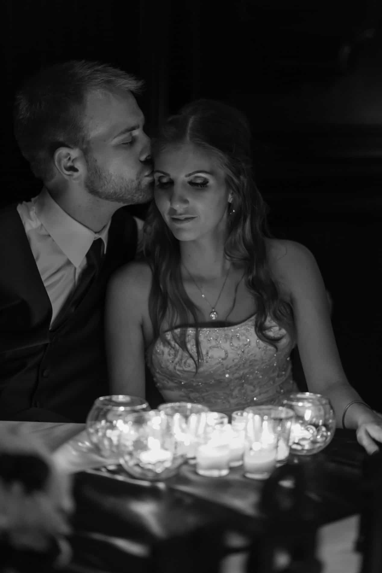 Couple kisses by candlelight at their 310 Lakeside Reception