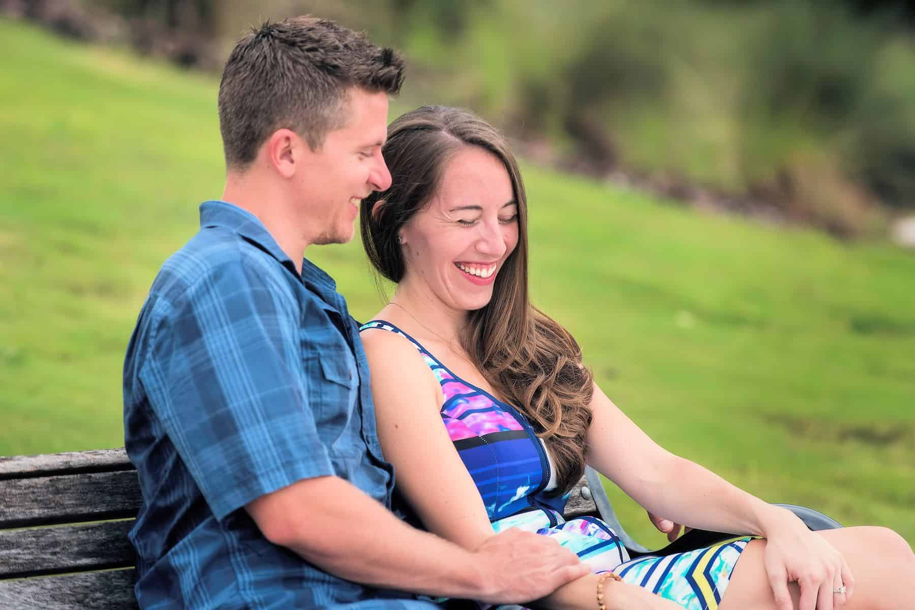 Couple laughs on Bench lakeside