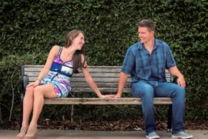 Cute Couple on a Bench in front of ivy wall