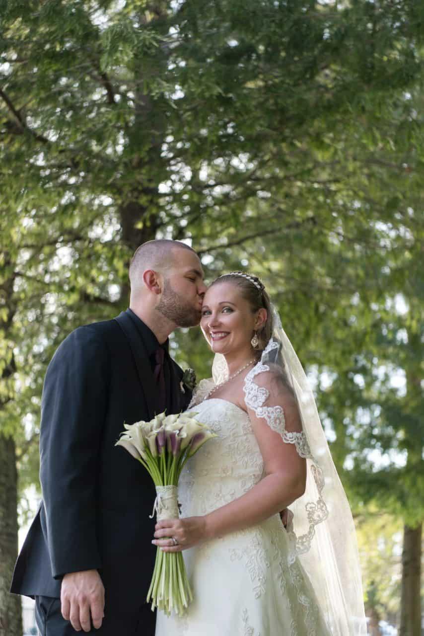 Groom kisses his new bride near Lake Lucerne