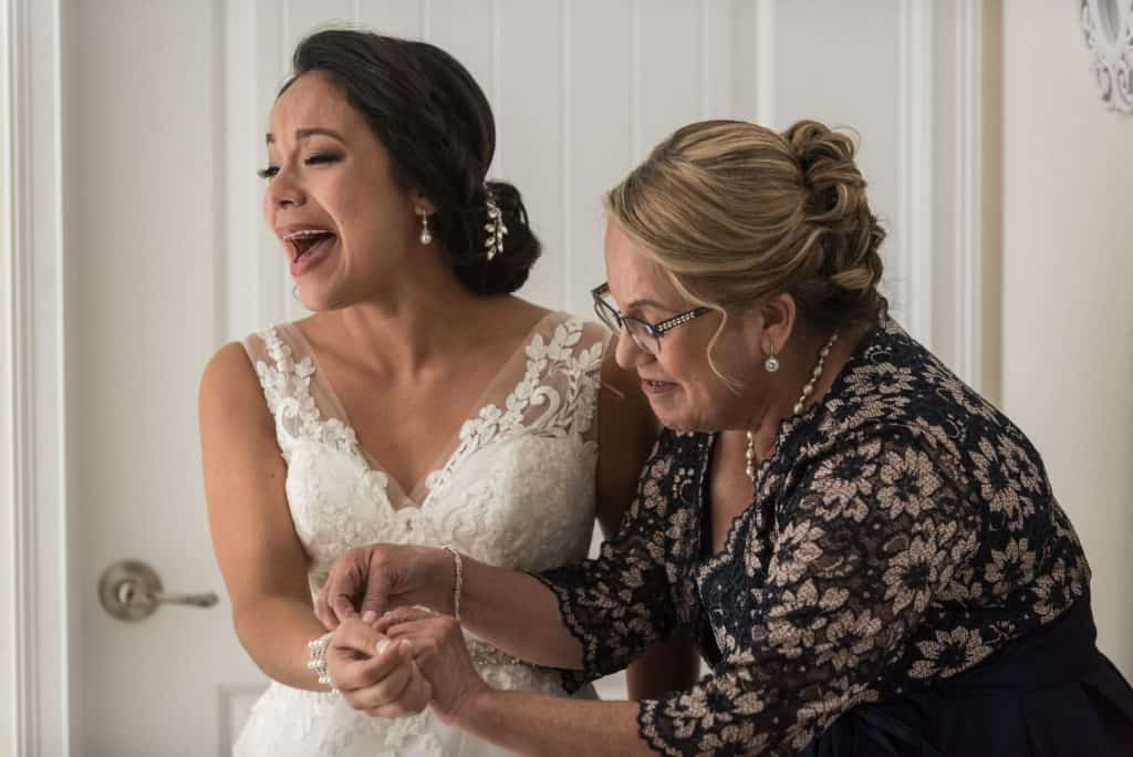Bride and her mom getting ready and laughing