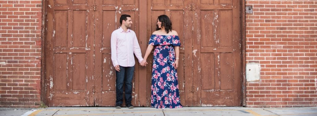 Engaged couple in front of red doors at the Garden Theatre
