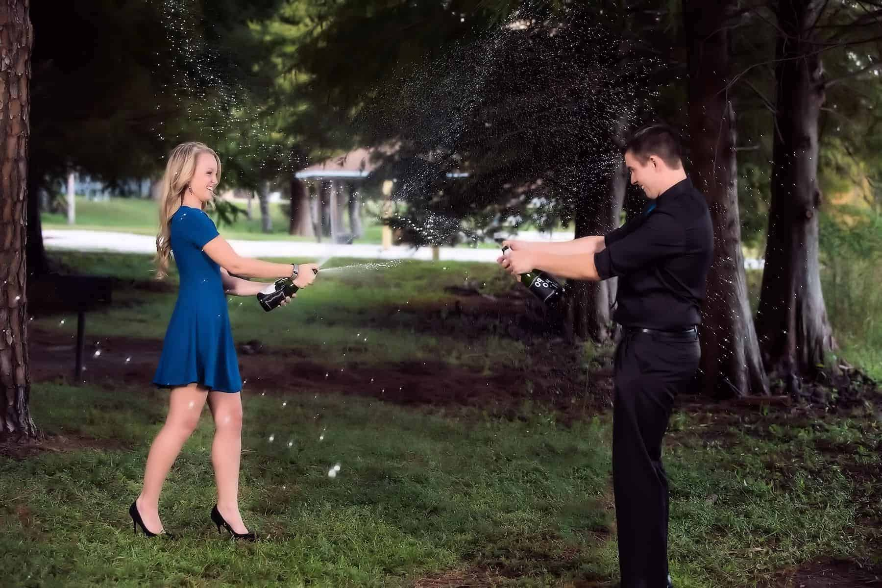 Couple popping the champagne on their engagement photos