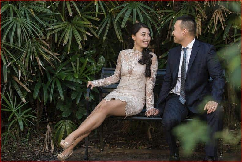 Engaged couple sitting on bench at Rollins College