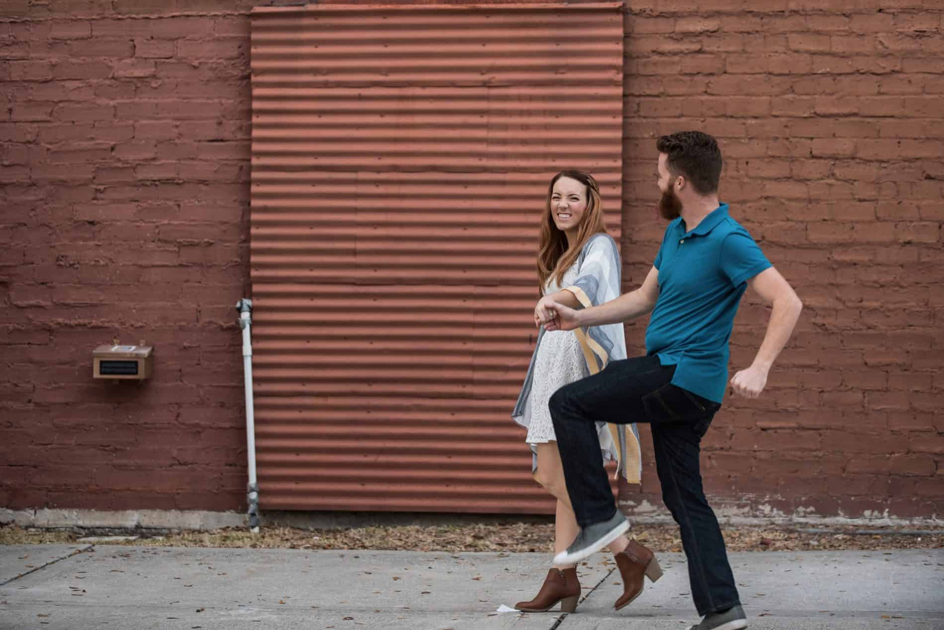 Engaged Couple walking in front of corrugated door