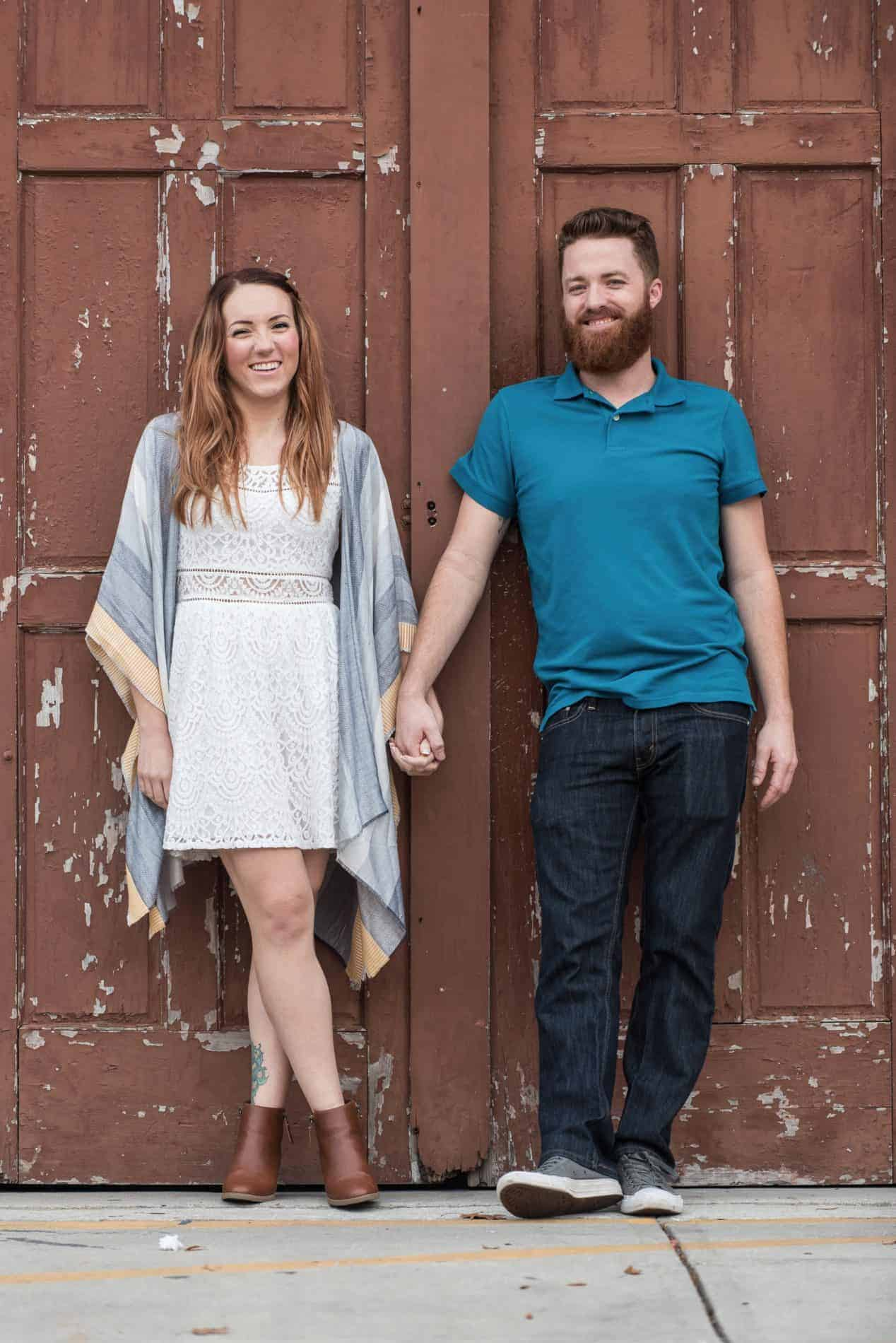 Smiling Engaged Couple in front of rustic door
