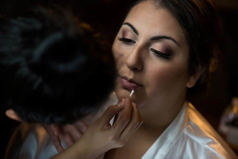 Bride gets final touchup from Make Up artist