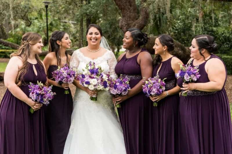 Bridesmaids playfully pose with the bride
