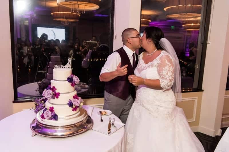 Bride and Groom kiss after cutting the cake