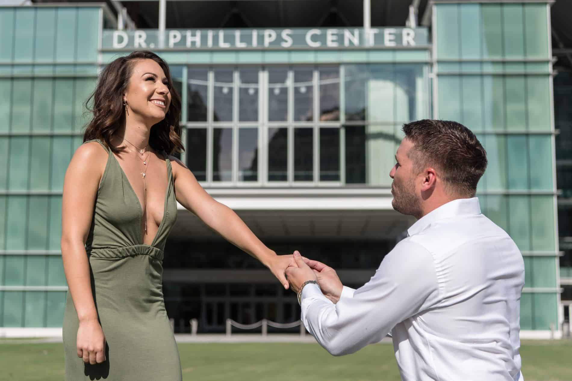 She reacts with a smile as he proposes