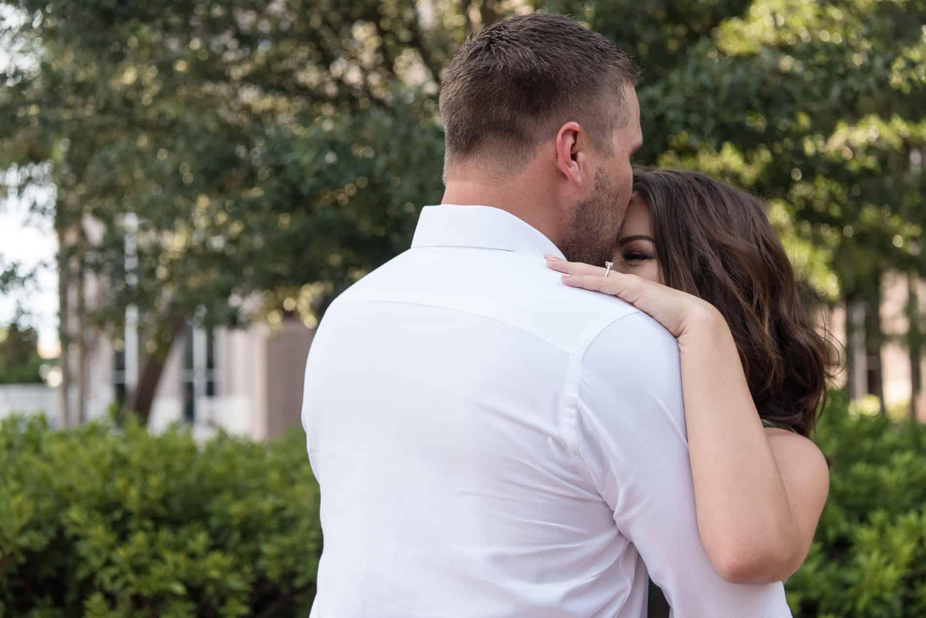 She hugs her fiance as he kisses her