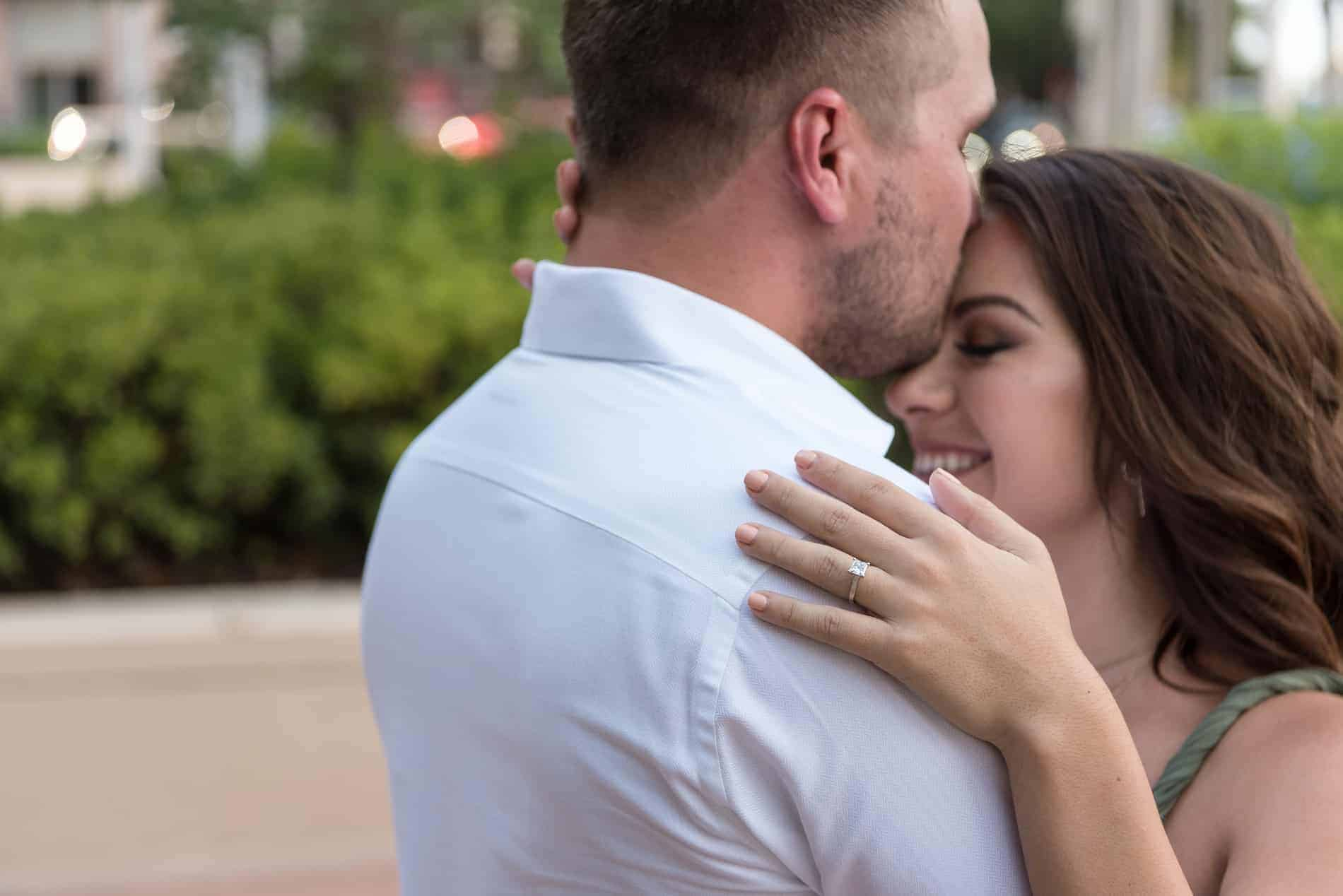 Bride smiles as she is kissed on the forehead
