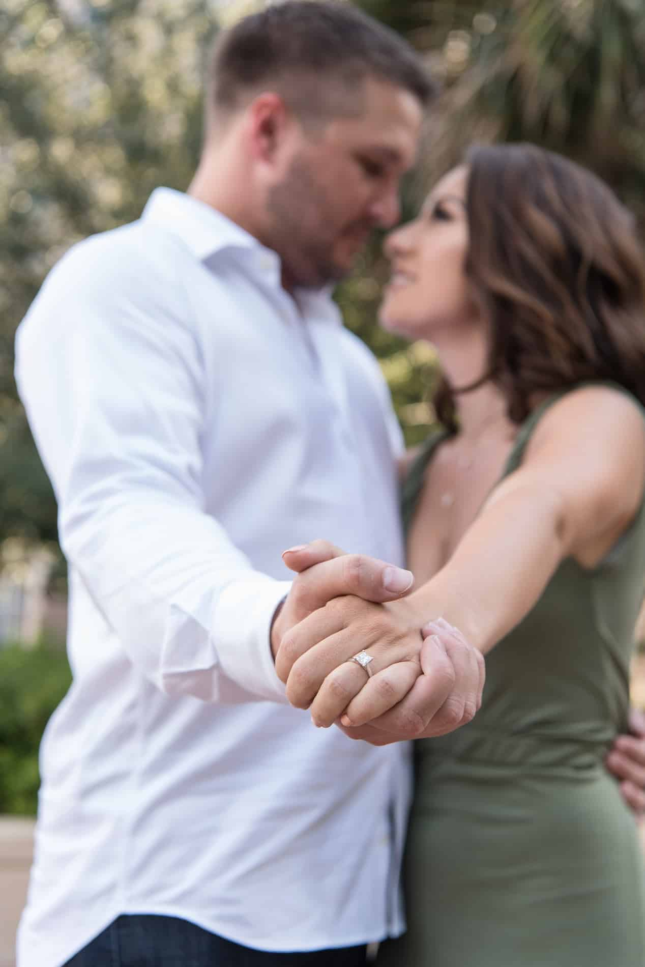 Focusing on the engagement ring during their Downtown Orlando Photos