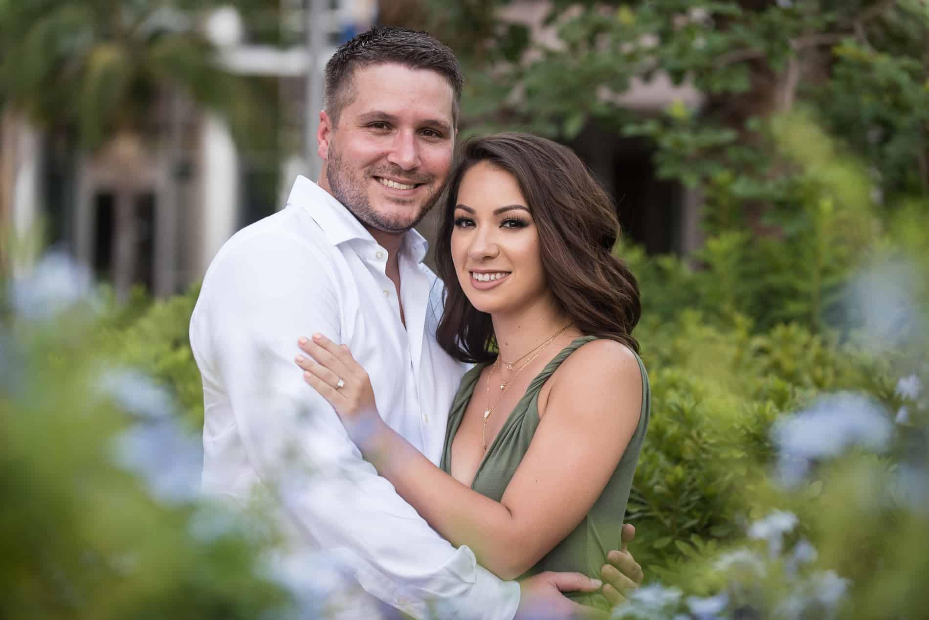 Engaged couple poses through the foliage of Orlando City Hall