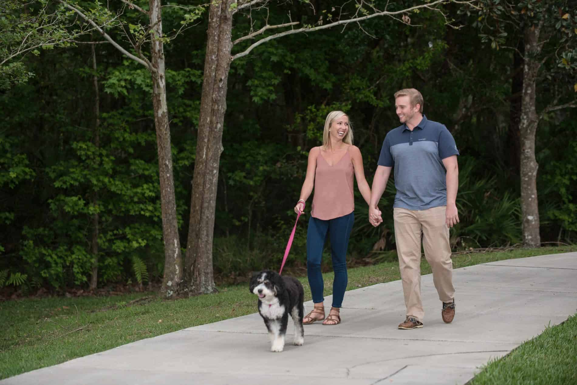 Couple walks their dog on the trails