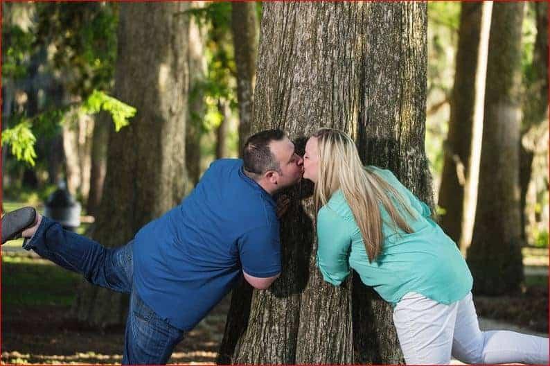 Couple playfully kiss in Kraft Azalea Garden