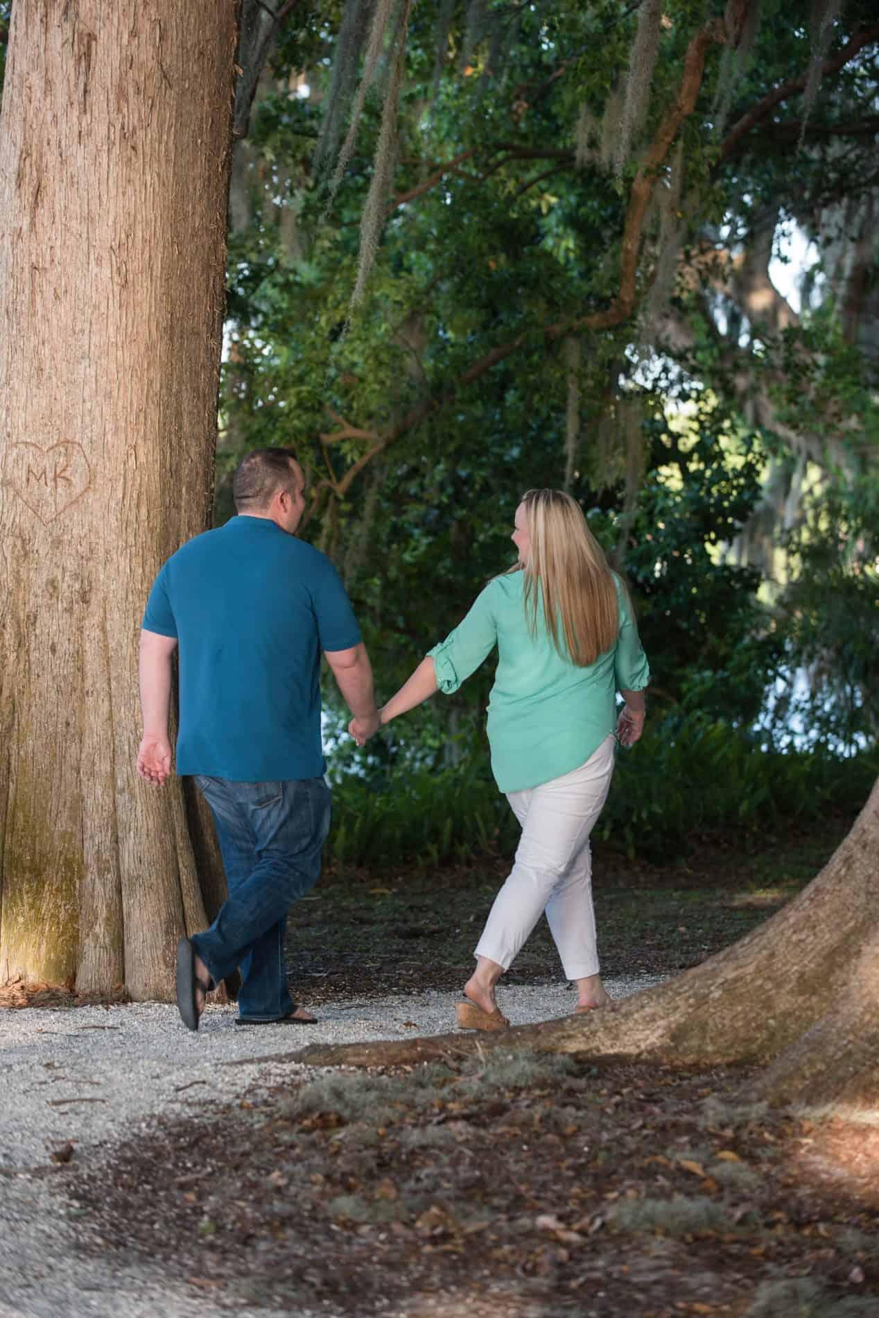 Engaged couple walking through park in Florida