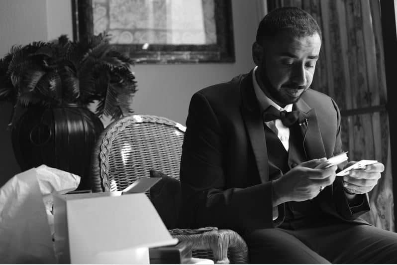 Photo of a Groom reading a letter from his bride