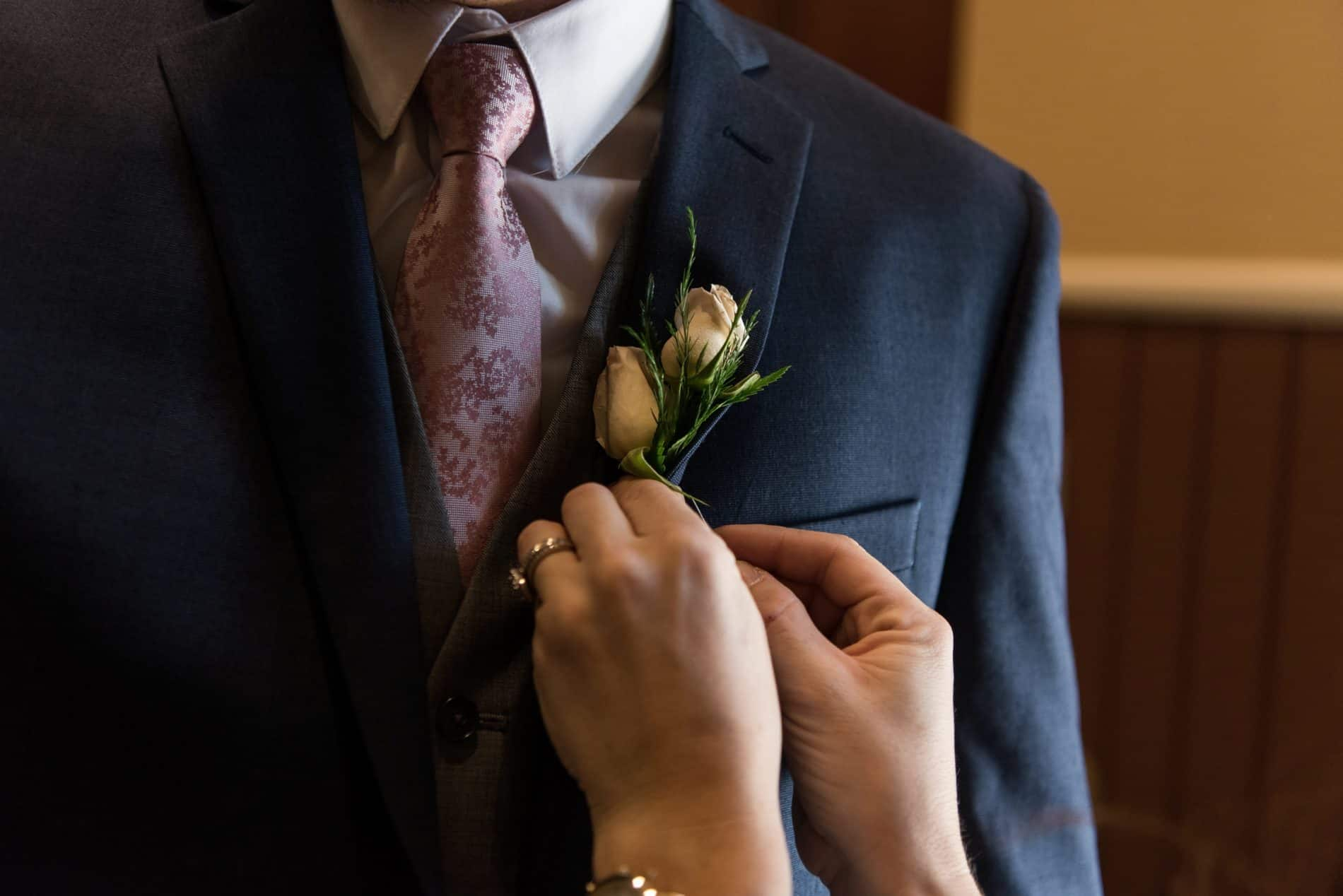 A Grooms Boutineer is placed on his tuxedo